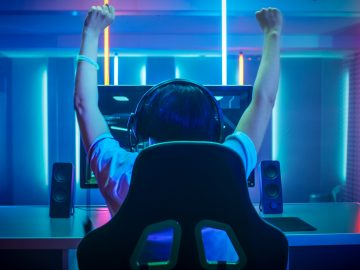 Professional Gamer Playing and Winning in First-Person Shooter Online Video Game on His Personal Computer. Footage Fade out into Bokeh. Room Lit by Neon Lights in Retro Arcade Style. Cyber Sport Championship.